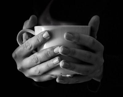 warming hands on mug of tea