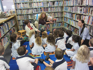 This photo shows the whole group watching me read the book .  You can see the backs of the students and me facing them.