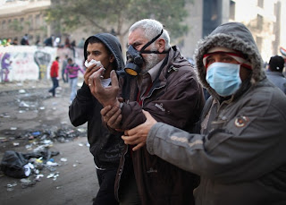 An injured protestor is led away during clashes