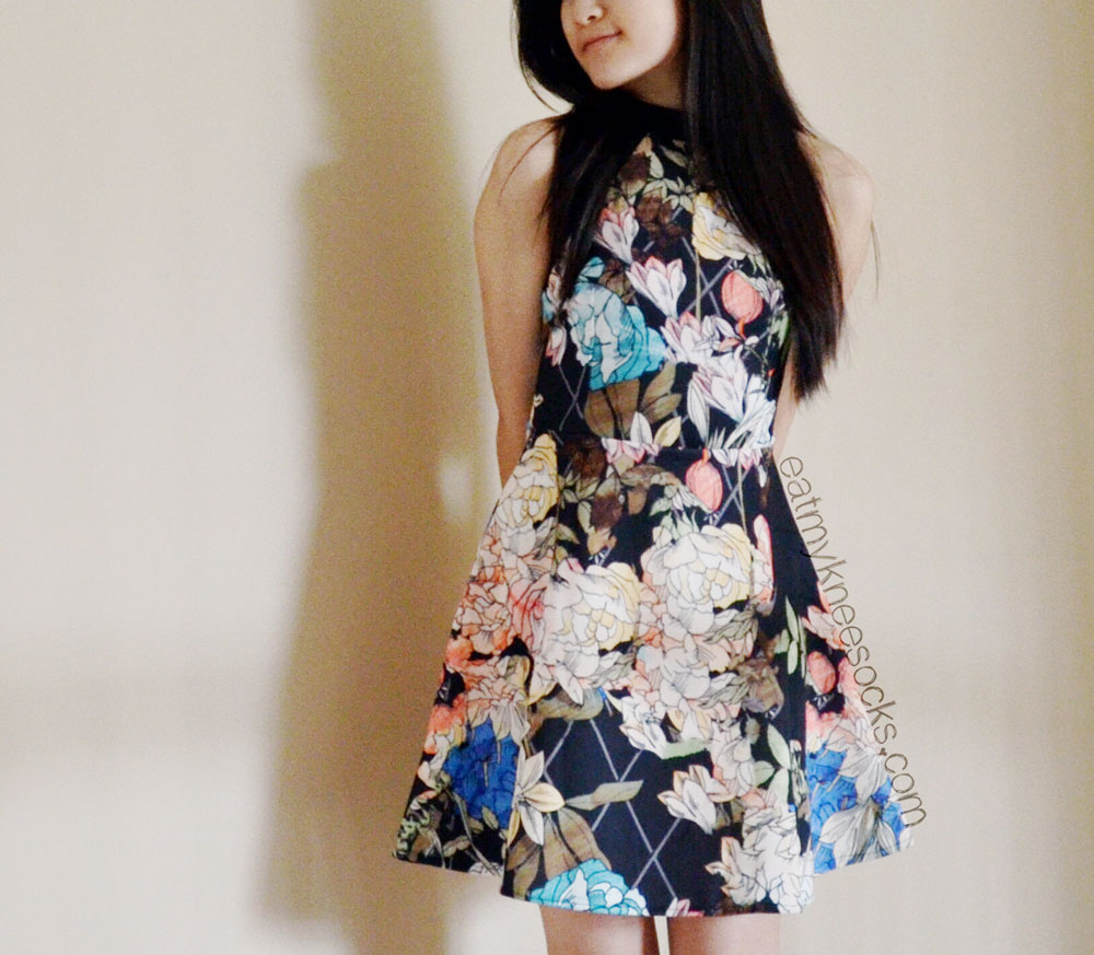 Another photo of the black scuba-knit floral dress from SheInside, which has a cute fit-and-flare silhouette.