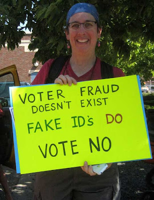 Woman holding hand-lettered sign reading Voter Fraud Doesn't Exist, Fake IDs Do