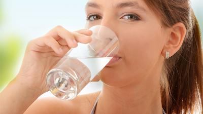 Mulher tomando líquido (água).