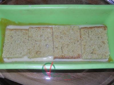 Poner en el molde un poco del batido y sobre él unos trozos de bizcocho.