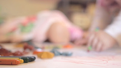 A young child sits on the floor with her crayons and colors a pretty picture