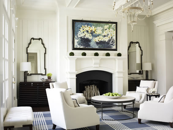 Symmetrical living room with white armchairs, a round table with wire legs, a large blue and white plaid rug, a fireplace with a white molded mantel with a black chest of drawers and a glossy black mirror on each side