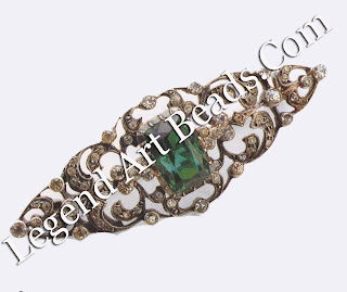 An open pierce work bar pin in chased silver, in an almost baroque style. Crystal stones are hand-set in clawed settings, with a large central simulated emerald stone. This type of brooch is typically French. The open pierce-work imitated the increasingly light feel of precious jewelry made in platinum. C.1910 £150-250 (S255-425)