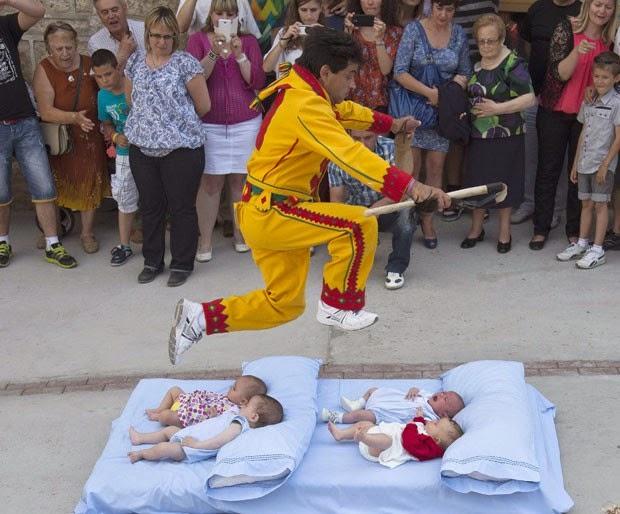 Homens vestido de diabo saltam sobre bebês