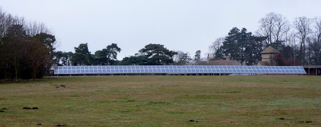view of solar panels in field obscuring farm
