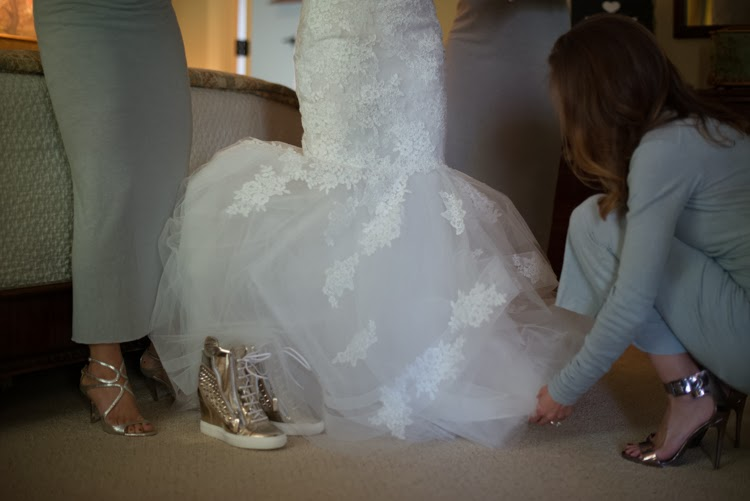 detail shot of brides shoes and bridesmaids' feet as they prep her Monique Lhuillier wedding gown