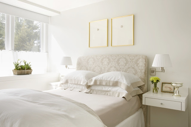 Bedroom with a white  upholstered headboard, large window and a white nightstand with a floating drawer