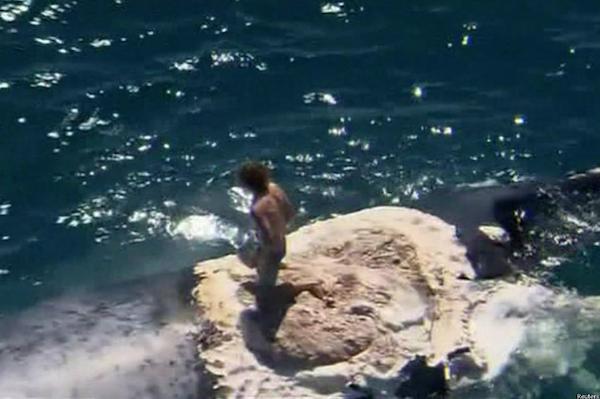 """VIDEO – Tipo """"surfea"""" sobre una ballena muerta en Australia"""