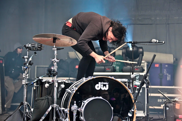 Kim of Matt & Kim standing on her seat and drumming during a performance at Copper Mountain.
