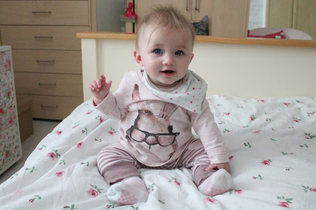 baby wearing pink top from Next with bunny wearing glasses and pink stripe trousers