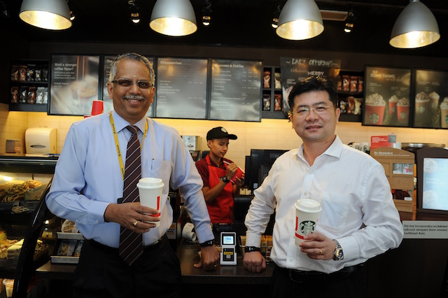 Maybank Group Head of Cards & Wealth, Mr. B Ravintharan and Visa Country Manager for Malaysia, Mr. Ng Kong Boon using their contactless wearables at Starbucks