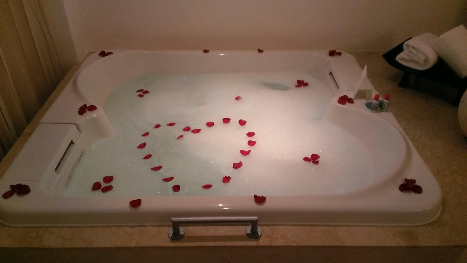 filled hot tub with rose petals in shape of hear
