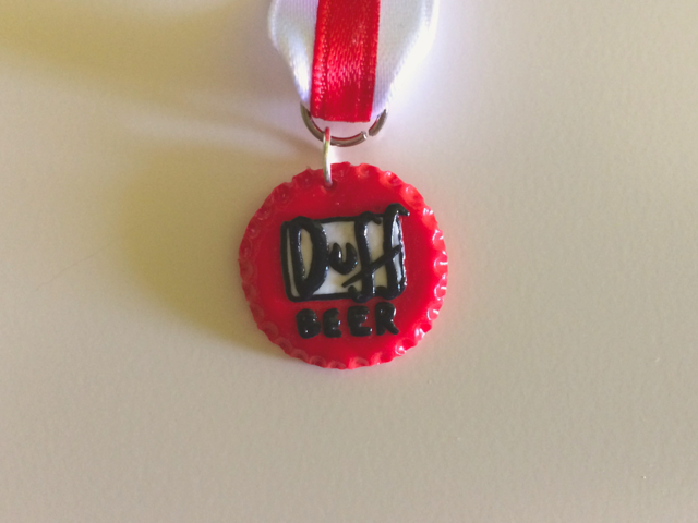 Foto medalla simulando chapa de botella Duff de Los Simpson