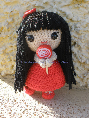 Muñeca realizada a crochet con vestido rojo y piruleta de fieltro