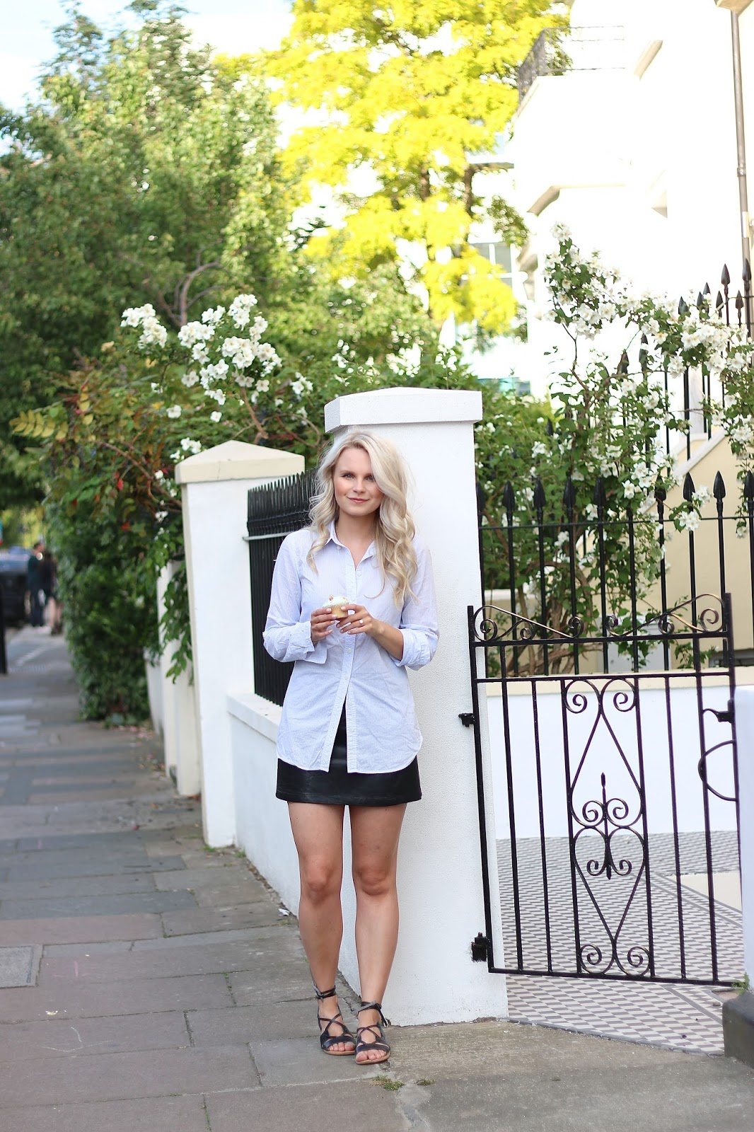 a girl wearing a leather skirt and preppy collar shirt poses for a pictures with a vanilla cupcake on notting hill, london on a summer day