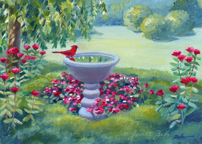 A northern cardinal at a birdbath