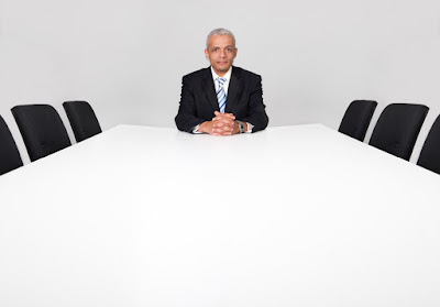 an executive is sitting alone at the head of the board room table