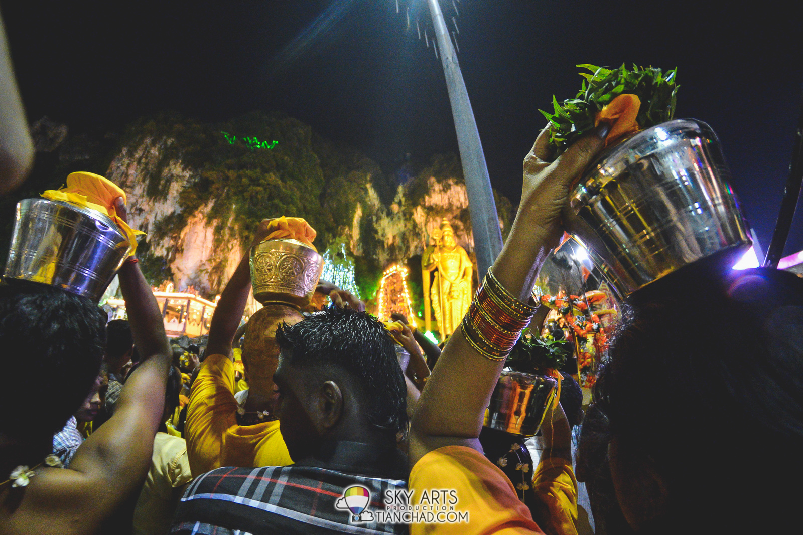 The devotees with milk container going up hill together.