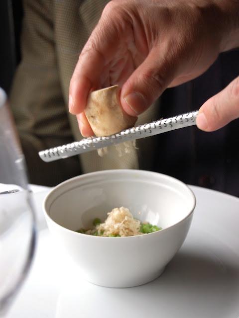Rallando sisa fresca sobre el plato de guisantes tiernos