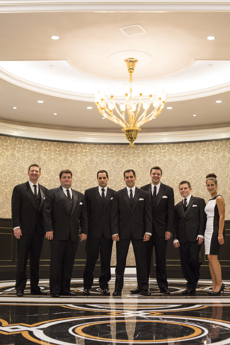 portrait of groom and groomsmen in new york palace hotel lobby