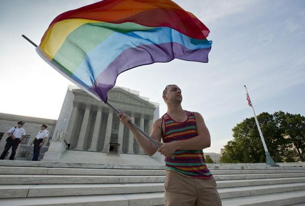 Defensor do casamento igualitário empunha bandeira na frente da Suprema Corte nesta quarta (26) em Washington (Foto: J. Scott Applewhite/AP)