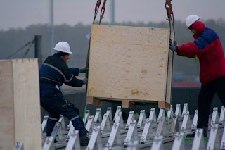 Unloading PV Panels on Roof with a Crane