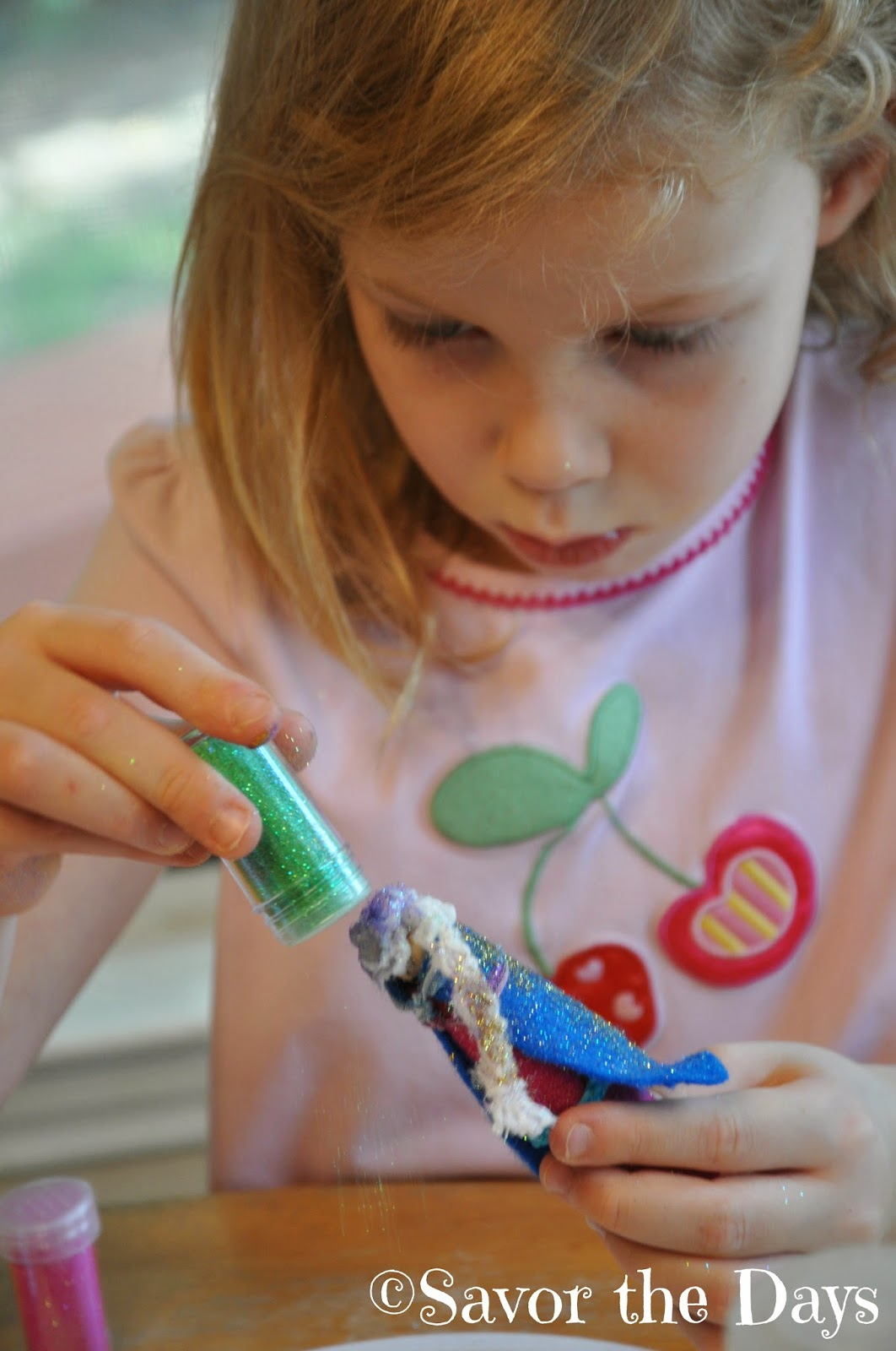 Little girl using green glitter
