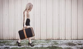 Teenaged prostitute walks down the street with a suitcase.