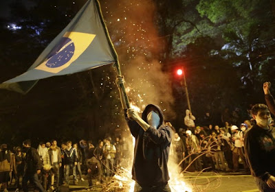 Protestos- jovem erguendo bandeira iluminado por fagueira ao fundo.