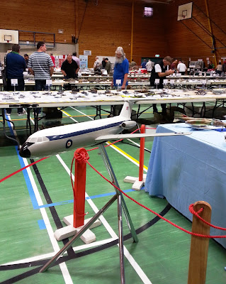 Scale model aeroplane in display in front of tables of scale models.