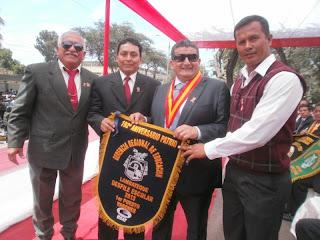 El presidente regional Humberto Acuña entrega el gallardete al colegio San José