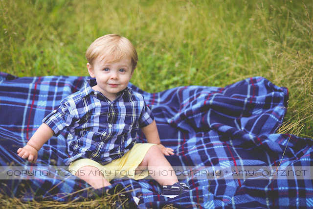 photo of toddler boy sitting on a blanket in a field