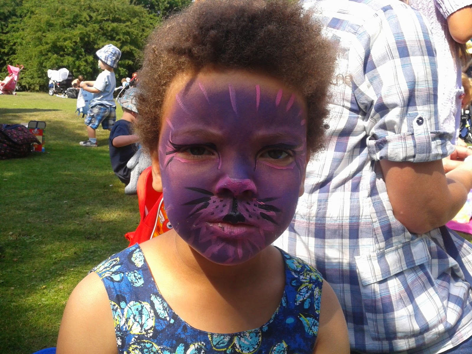 madam wearing face paint to look like a cat. In purple and pink.