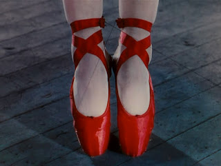 See those threads...?  Cool 1948 special effects for undoing the laces, then playing the film backwards to make it look like the red shoes attached themselves to her feet by magic.