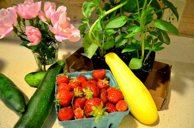 yellow squach, red strawberries, green cucumbers and basil, pink roses