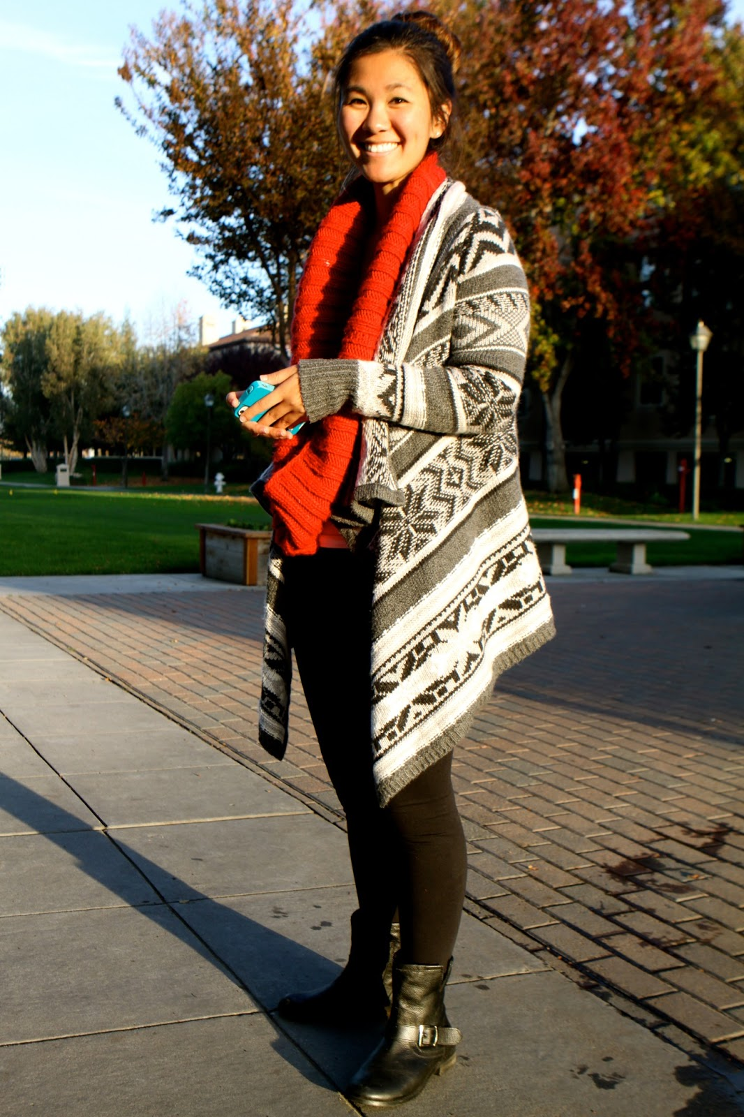 Santa Clara University student Jessica wears a gray and white aztec pattern christmas cardigan combo with a red infinity loop scarf black tights and black boots