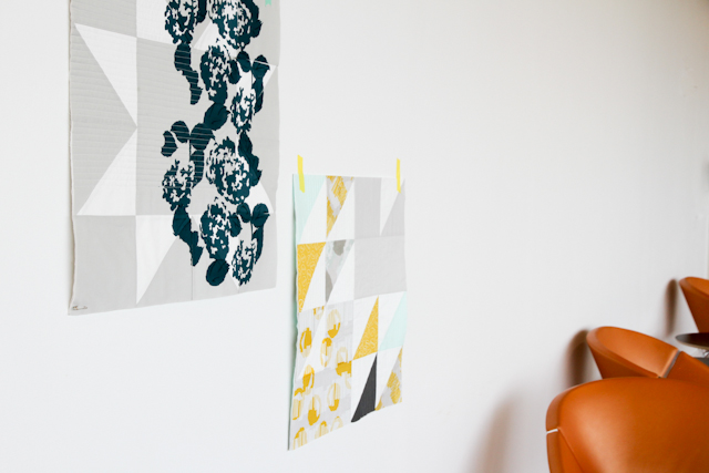 two printed modern quilts taped to the wall
