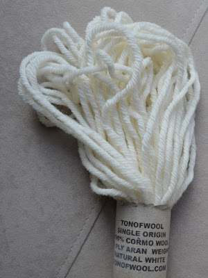 A close-up photo of one half of the skein with the paper label which says: TONOFWOOL SINGLE ORIGIN 100% CORMO WOOL 10 PLY ARAN WEIGHT NATURAL WHITE TONOFWOOL.COM