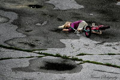Zdjęcie wykonane z żyrafiej perspektywy, dziecko na rowerze, upadek, kompozycja