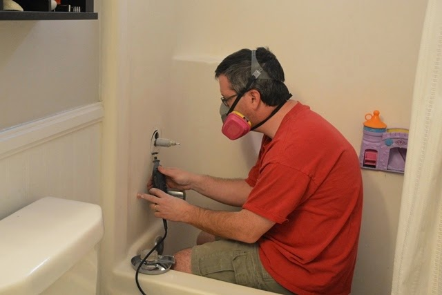 cutting into a shower wall with a rotary tool and a 3M respirator