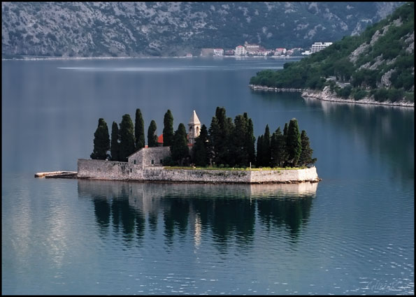Small island in the Bay of Kotor reflected in the water.
