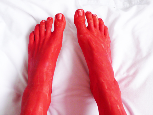 Red face painted feet on a white sheet.