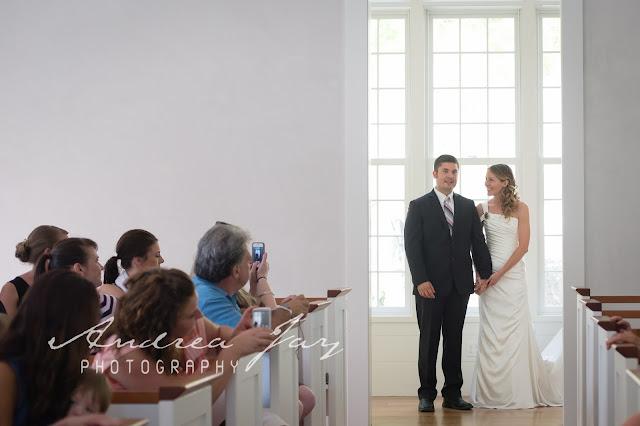 Groom escorts bride down aisle
