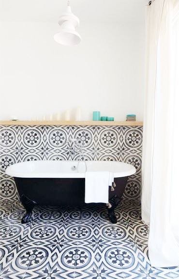 Black freestanding tub with Moroccan inspired tile floor