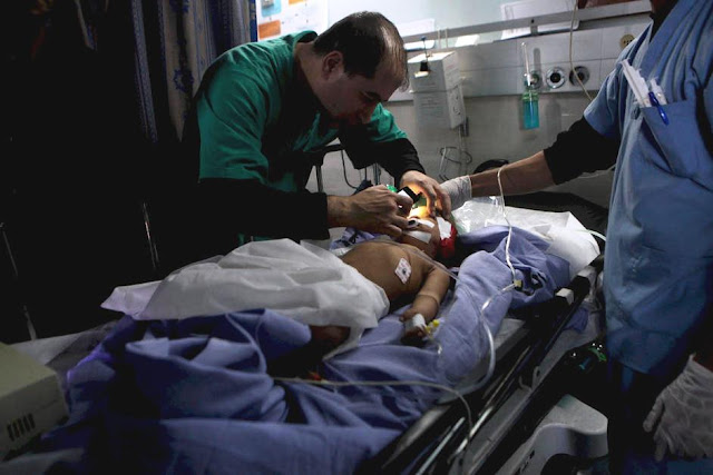 Palestina - Médico usa luz do celular para cuidar de criança ferida