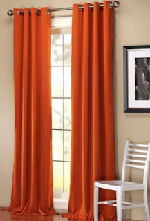 Custom orange grommet draperies with puddling