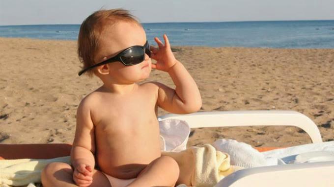 anak laki-laki bermain pasir di pantai